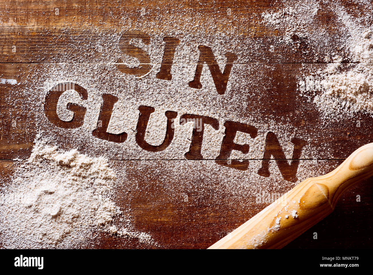 high-angle shot of a wooden table sprinkled with a gluten free flour where you can read the text sin gluten, gluten free written in spanish, next to a - Stock Image