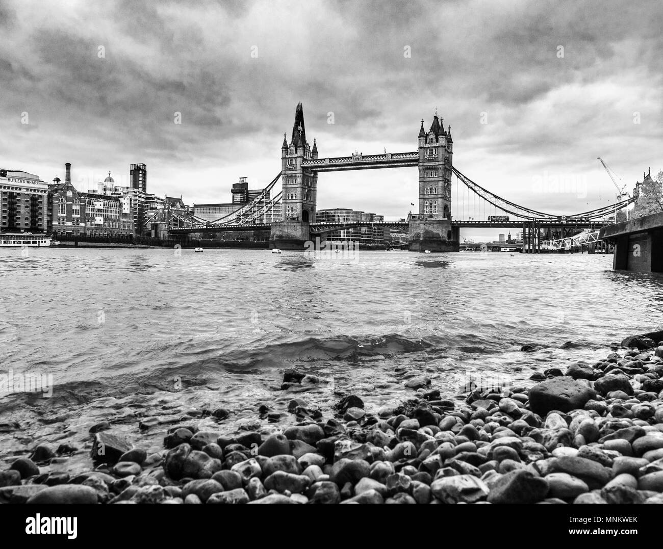 North pebbled shore of the river Thames in London with Tower Bridge. The top of the Shard can just be seen in the distance. - Stock Image