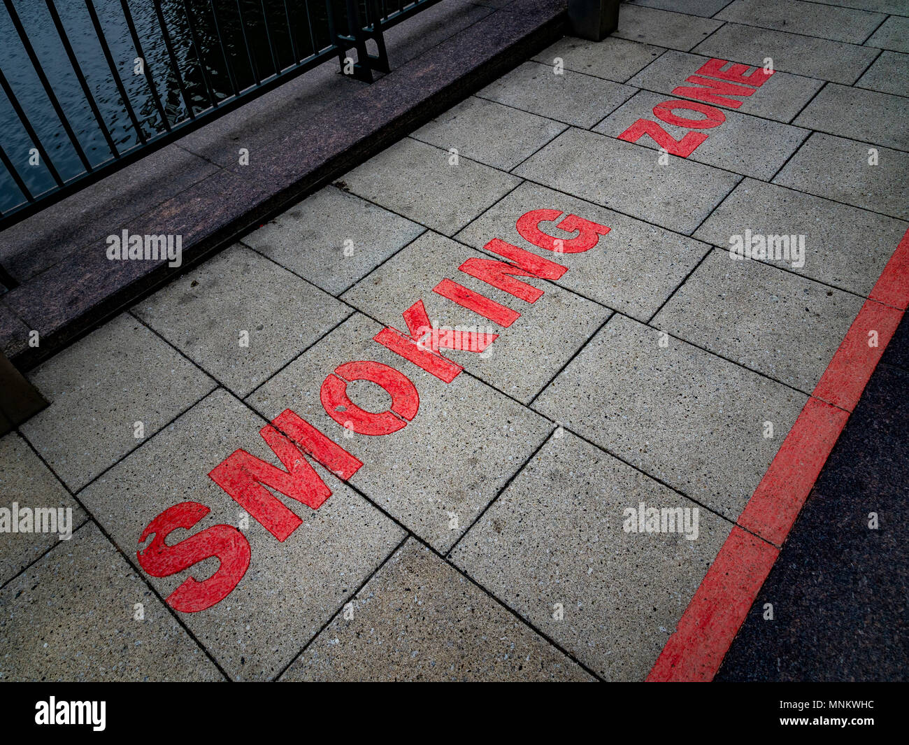 Smoking Zone sign in red lettering on pavement, London, UK. - Stock Image