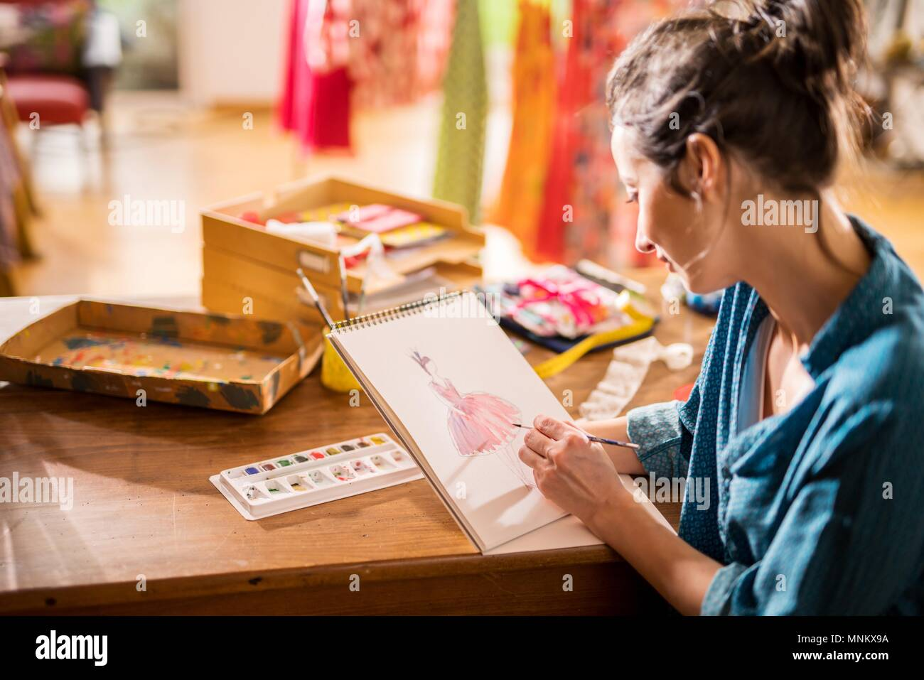 Fashion designer working on a new model, in her studio - Stock Image