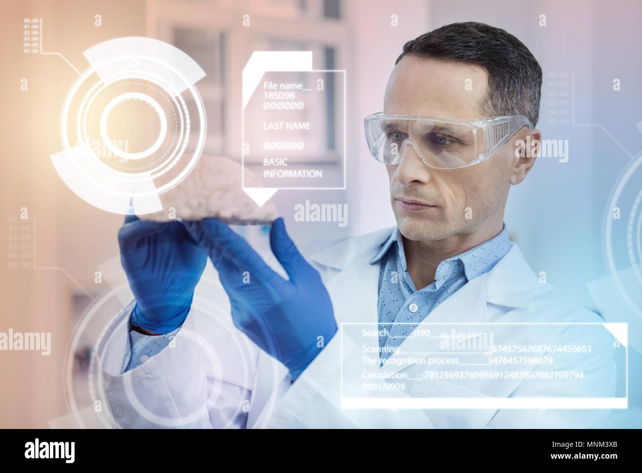 Attentive doctor looking at the brain miniature while working in glasses - Stock Image