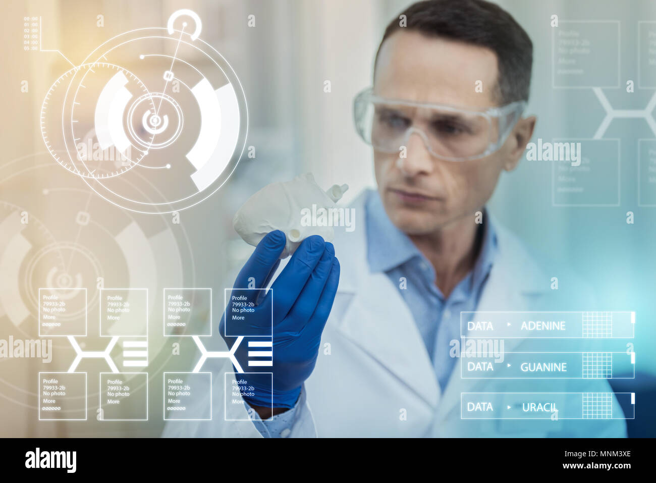 Worried doctor frowning and looking at the realistic miniature heart - Stock Image