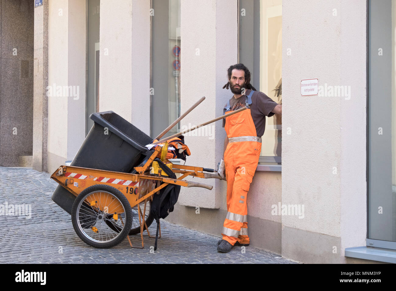 A sanitation man in a  reflective uniform takes a break in Regensburg, Germany. - Stock Image