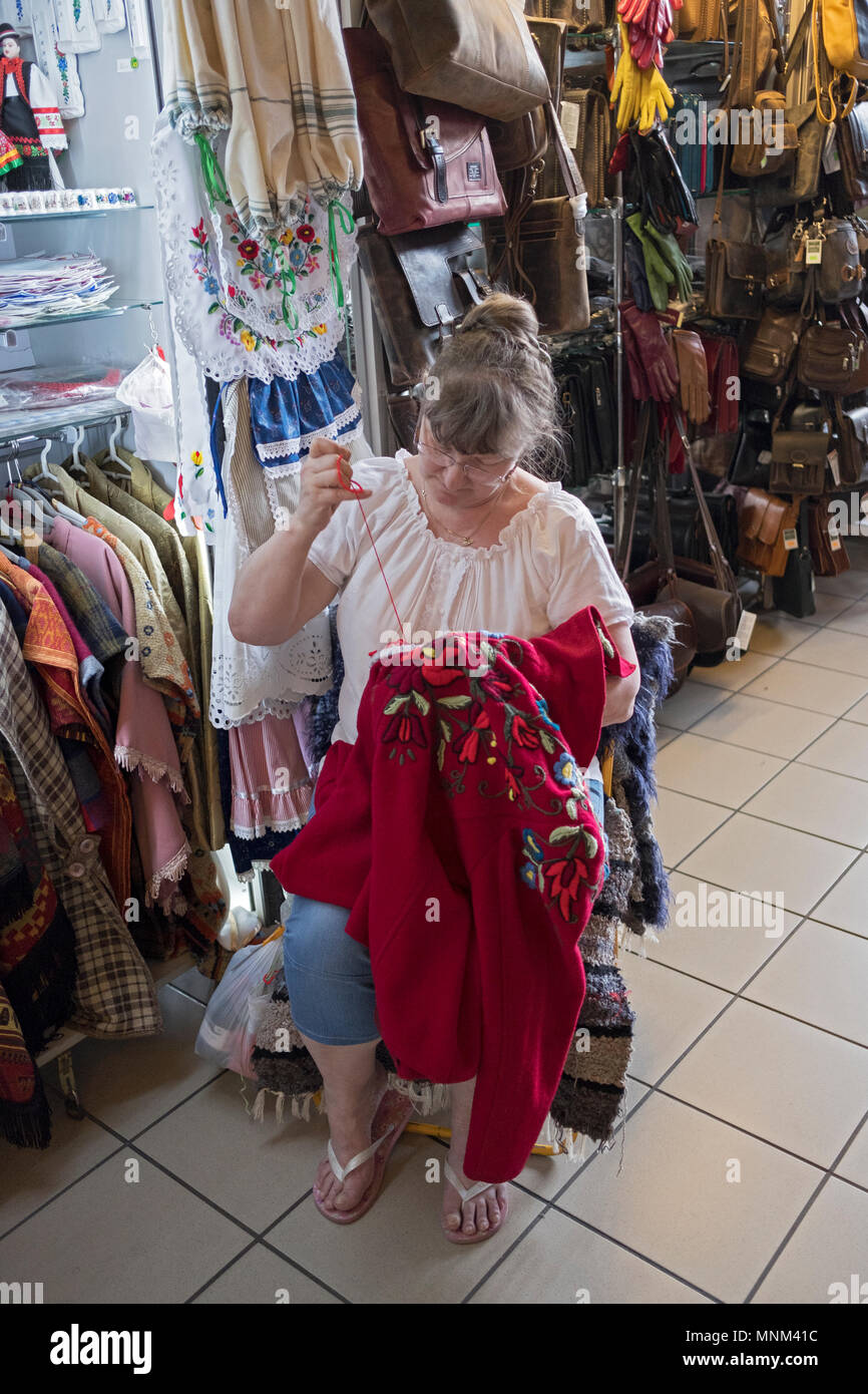 A vendor at the Central Market in the Pest section of Budapest, Hungary sewing embroidery on a jacket she is selling. Stock Photo