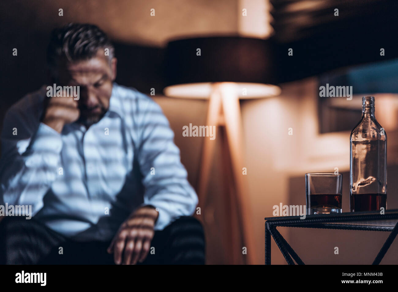 Bottle and glass with alcohol in the foreground and wasted addict sitting in the back (blurred) - Stock Image