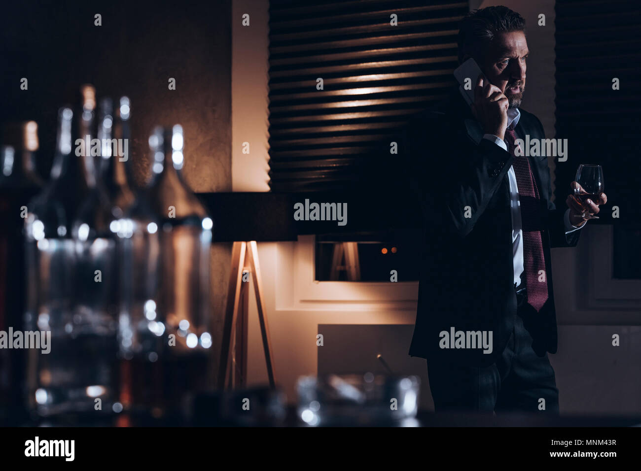 Stressed middle-aged man in a suit talking on the phone and holding a glass of alcohol while standing in a dark room with empty booze bottles in a blu - Stock Image