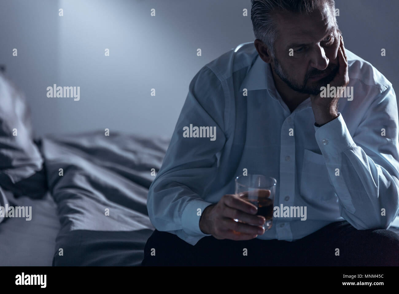 Close-up of a man with midlife crisis sitting on a bed with one hand on his chin and holding a glass of alcohol in the other - Stock Image