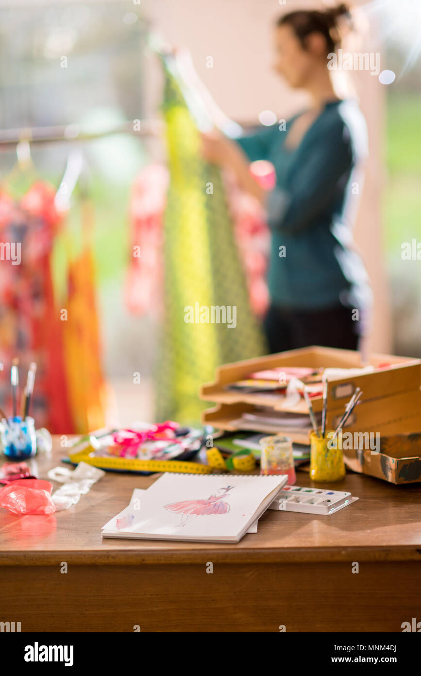 Fashion designer working on a new model in her studio, she designs a new dress. Focus on the table - Stock Image