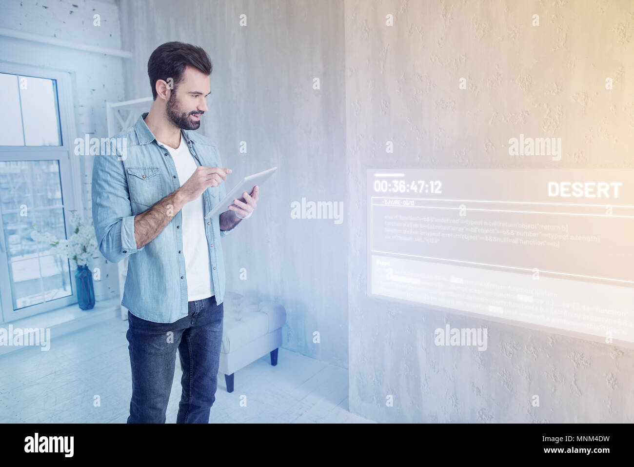 Cheerful blogger looking happy while standing with a modern tablet - Stock Image