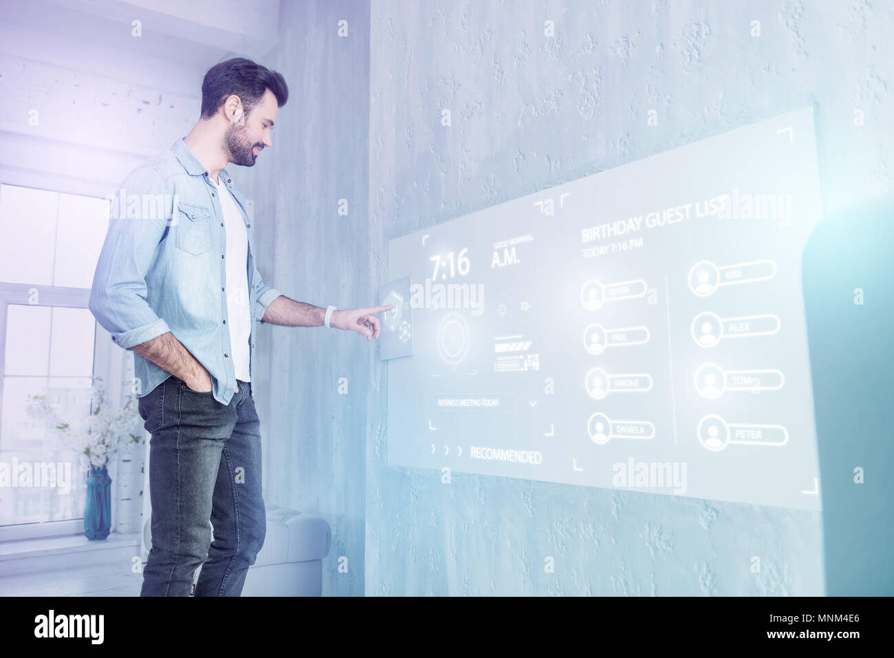 Young web developer touching a futuristic screen while working at home - Stock Image