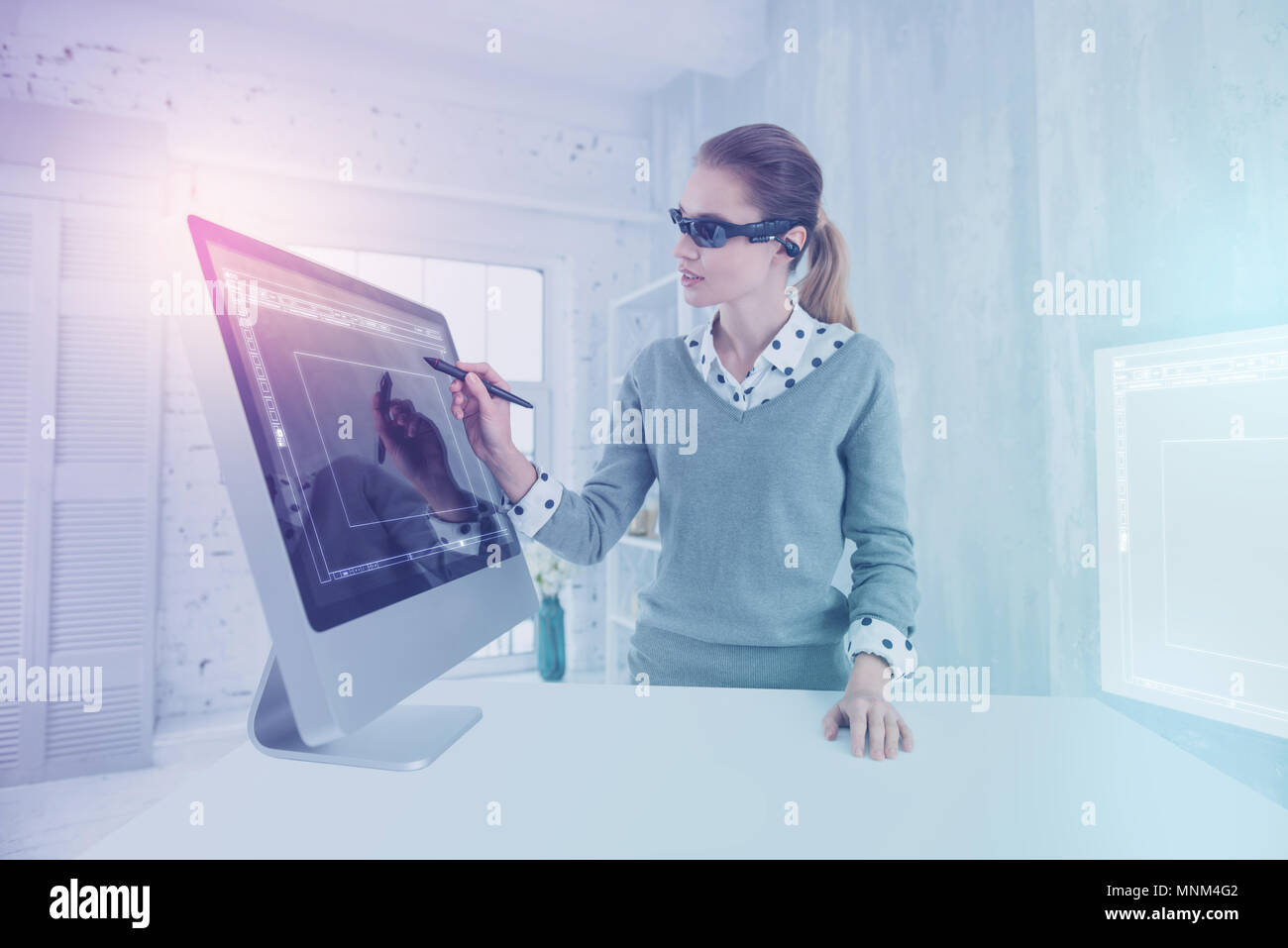 Calm designer wearing virtual reality glasses while drawing - Stock Image