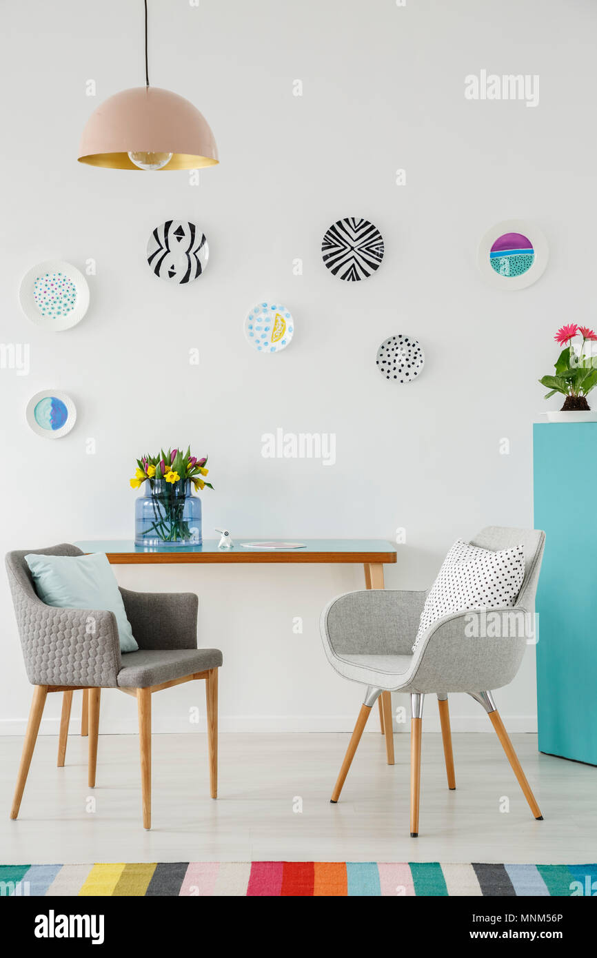 Creative Living Room Interior With Plates On The Wall Table Grey Armchairs Flowers And Colorful Rug Stock Photo Alamy