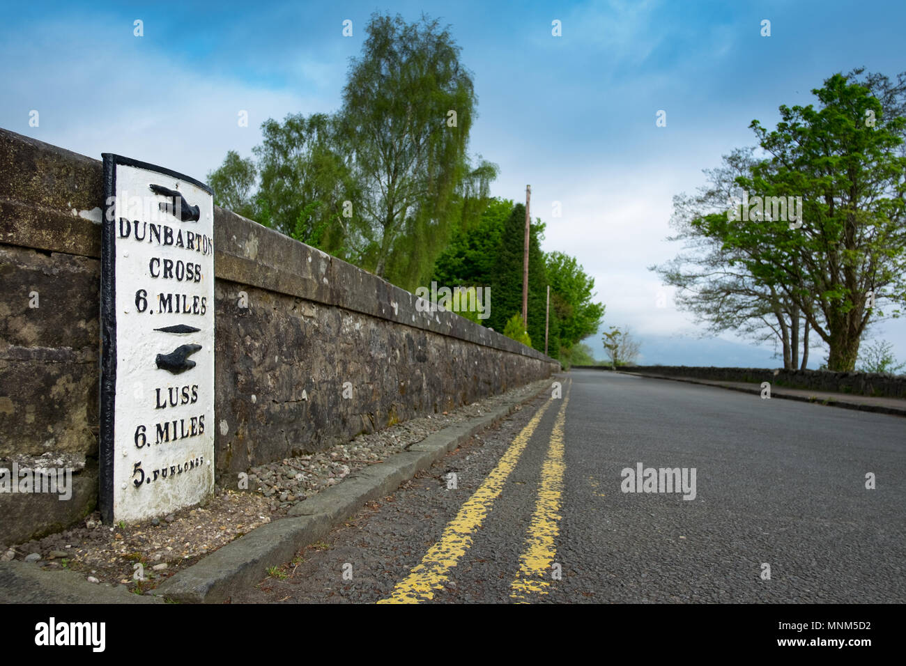Milestone next to deserted road on the banks of Loch Lomond - Stock Image