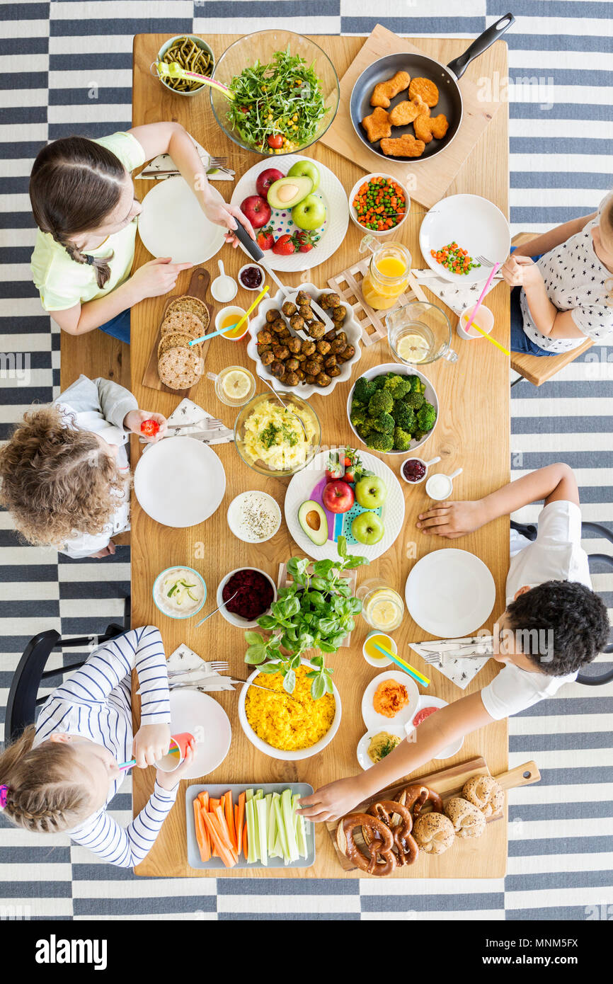 Top view on kids eating healthy dinner at table during birthday party - Stock Image