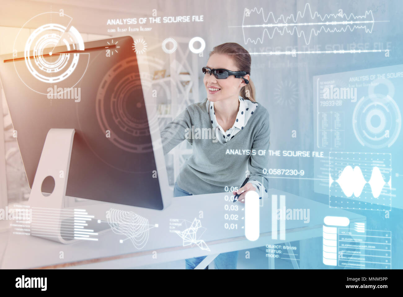 Positive designer smiling while looking at the screen of her convenient computer - Stock Image