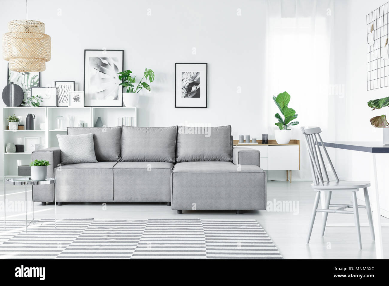 Scandinavian living room interior with a comfy corner sofa, paintings, plants and striped carpet - Stock Image