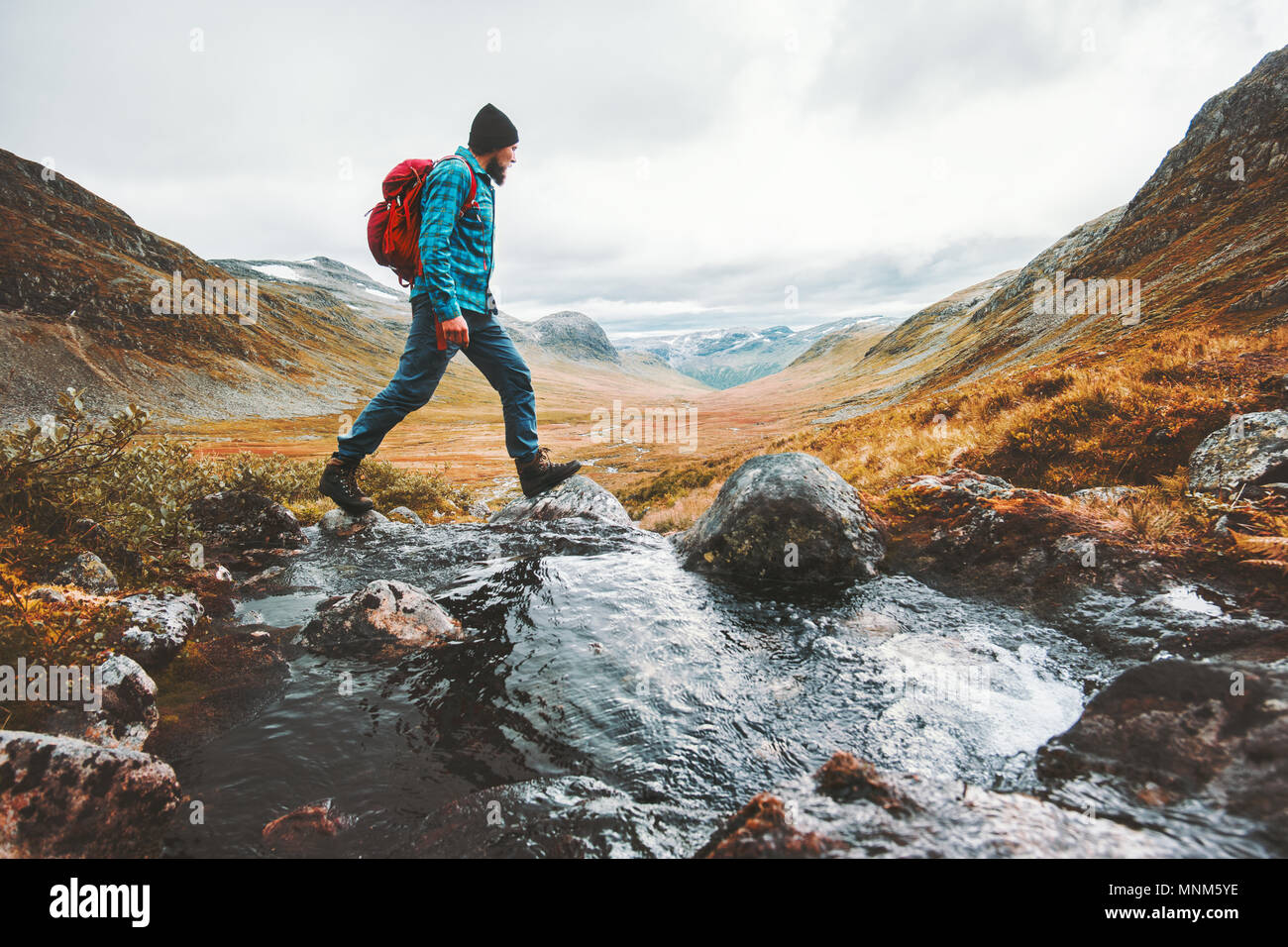 Man solo traveling backpacker hiking in scandinavian mountains active healthy lifestyle adventure journey vacations - Stock Image