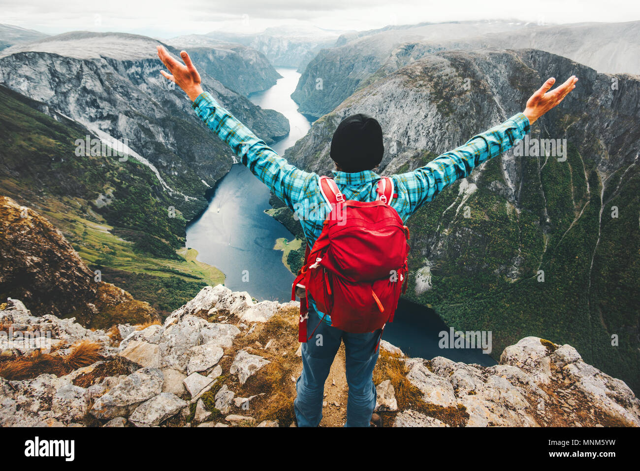 Traveler Man on the top of mountain success raised hands healthy Lifestyle Travel adventure vacations above Naeroyfjord in Norway - Stock Image