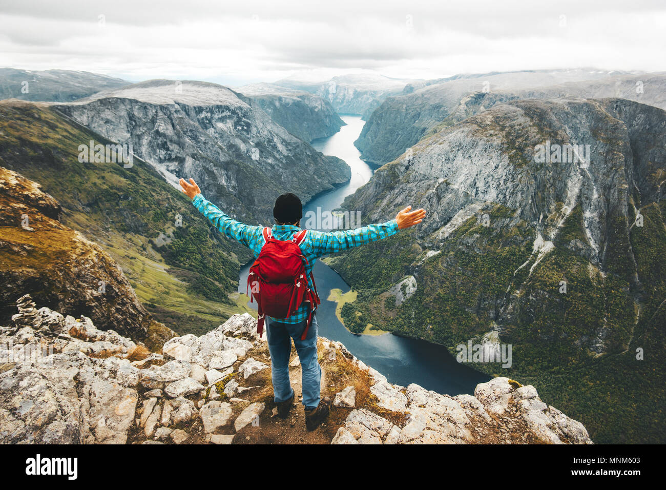 Happy Man backpacker on mountain summit traveling in Norway Lifestyle Travel adventure active vacations above Naeroyfjord success wellness healthy lif - Stock Image