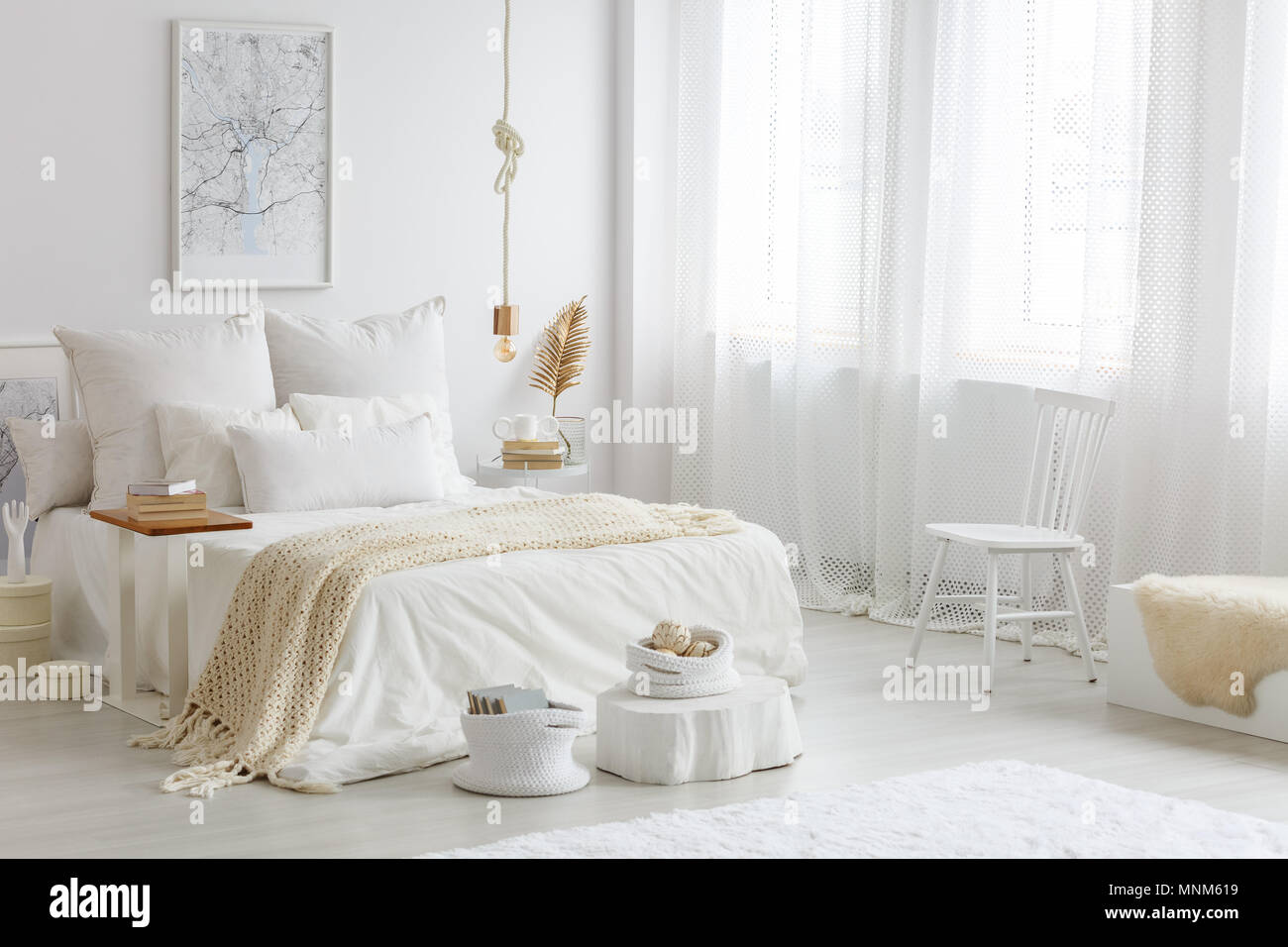 Wooden chair standing by the window with curtains in white bedroom ...