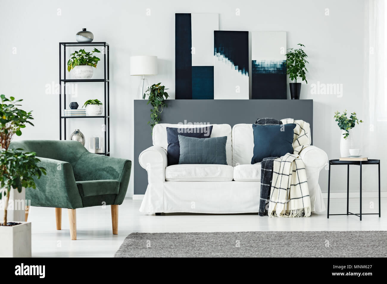 Green armchair, white sofa, plants and grey wall in a modern living ...