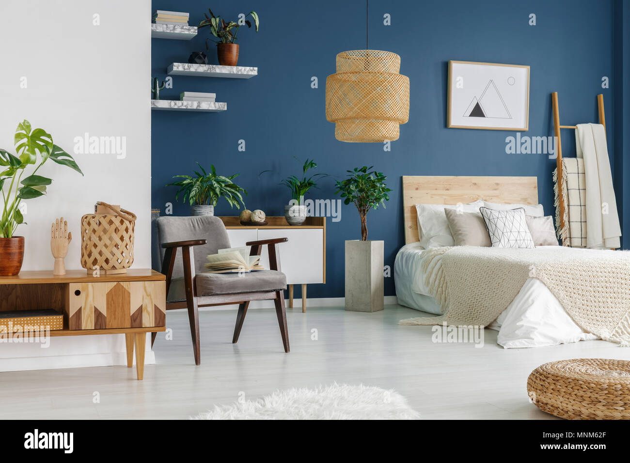 Wooden Furniture And Marble Shelves In Bedroom Interior With Green Plants Double Bed And Grey Armchair Stock Photo Alamy