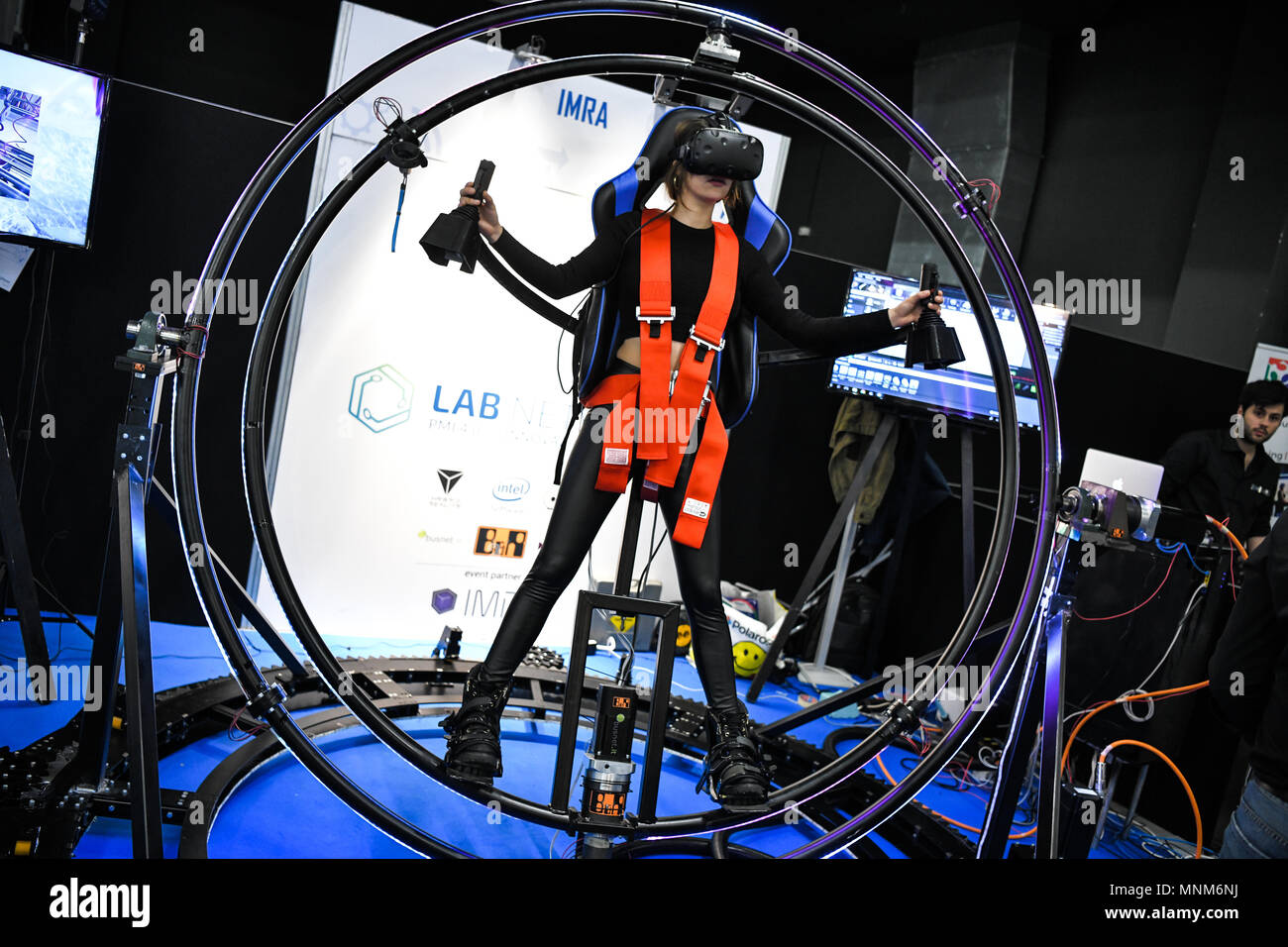 Milan, Italy - 17 May 2018: A woman tries VITRUVIAN VR, a gyroscope Virtual Reality simulator,  on display during the Technology Hub 2018. - Stock Image