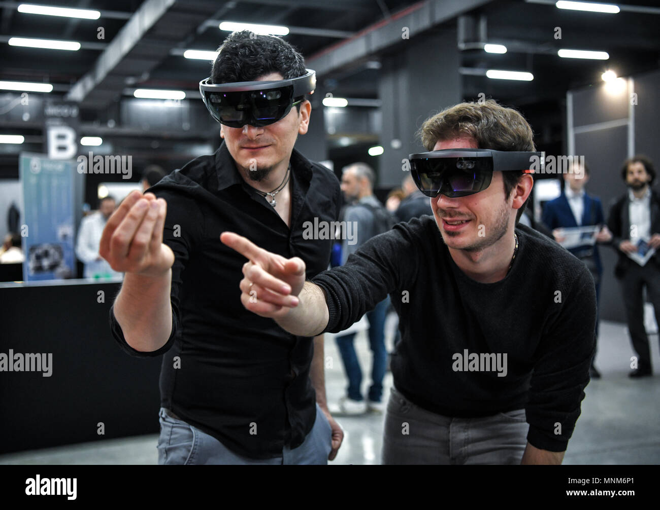 Milan, Italy - 17 May 2018: Two young men wearing VR Virtual Reality headsets gesticulate and interact together  during the Technology Hub 2018. - Stock Image