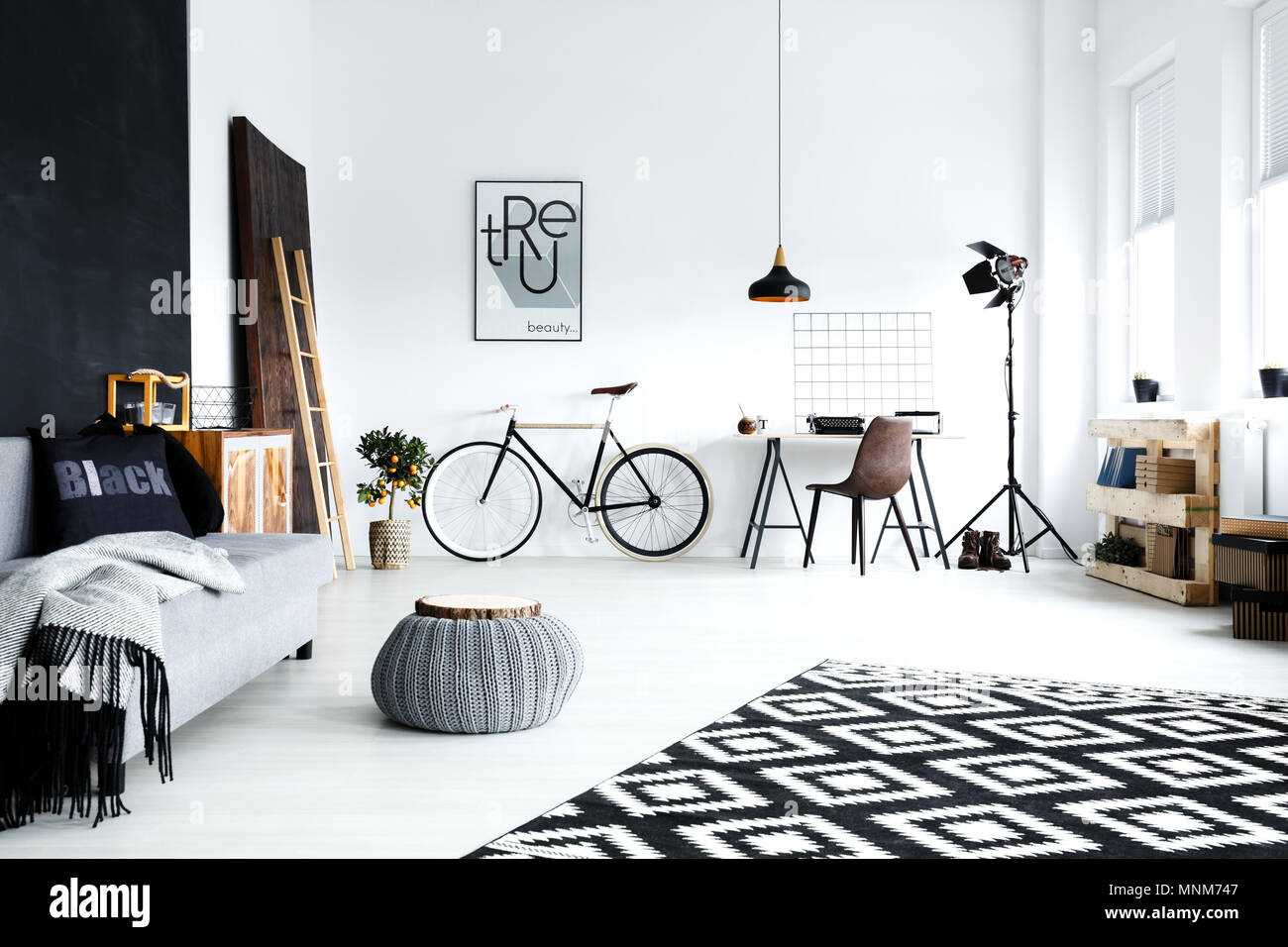 Open plan, white studio flat with sofa, bike, pouf, desk - Stock Image