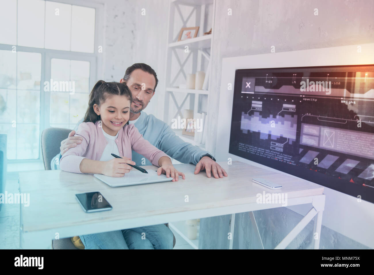 Cheerful father smiling and his daughter doing homework - Stock Image