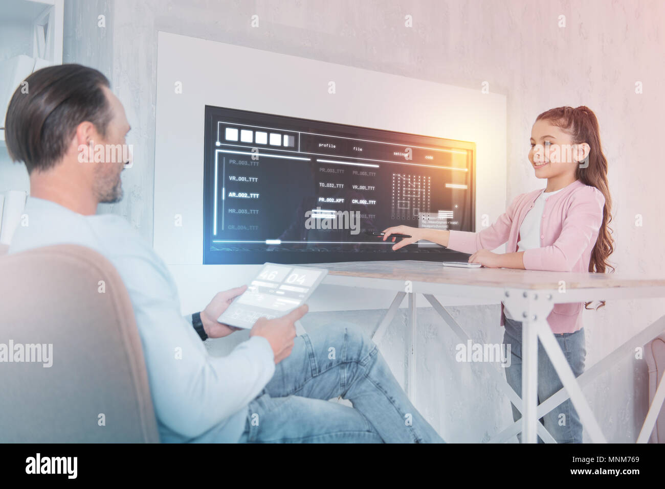Clever girl smiling while talking to her professional teacher - Stock Image