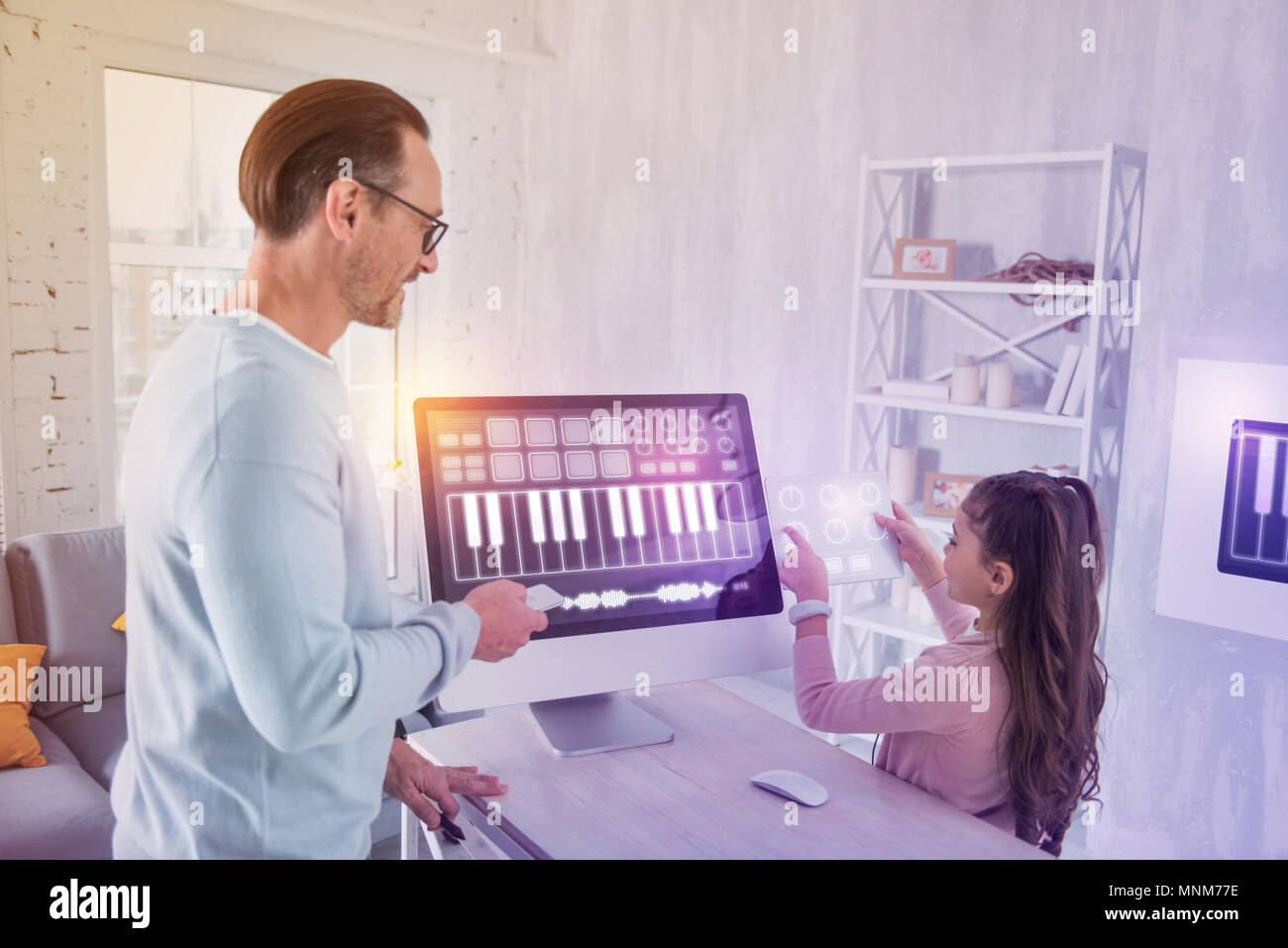 Enthusiastic pupil showing a tablet while having a lesson - Stock Image