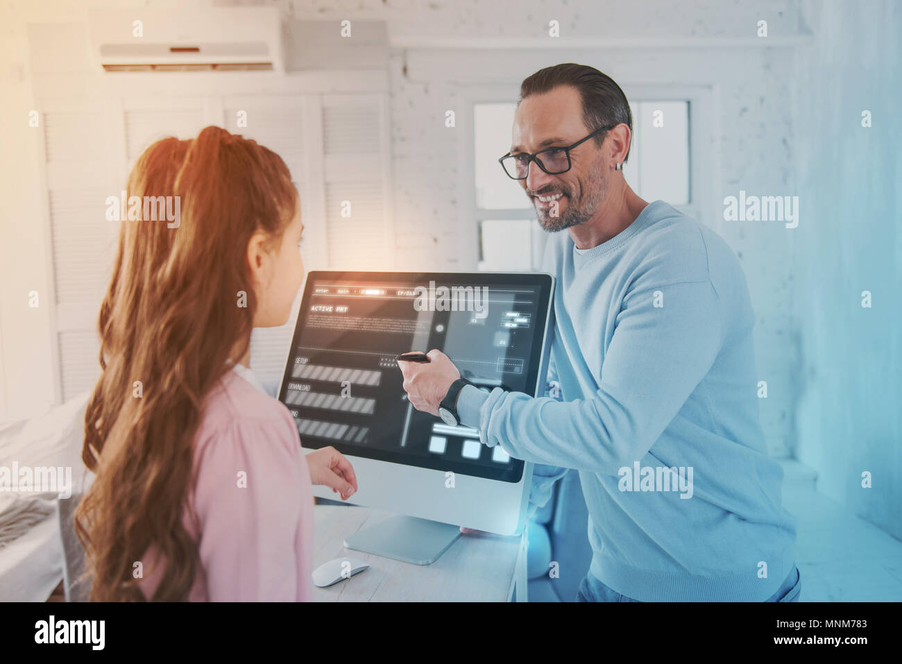 Emotional teacher pointing to the screen and looking attentively at his pupil - Stock Image