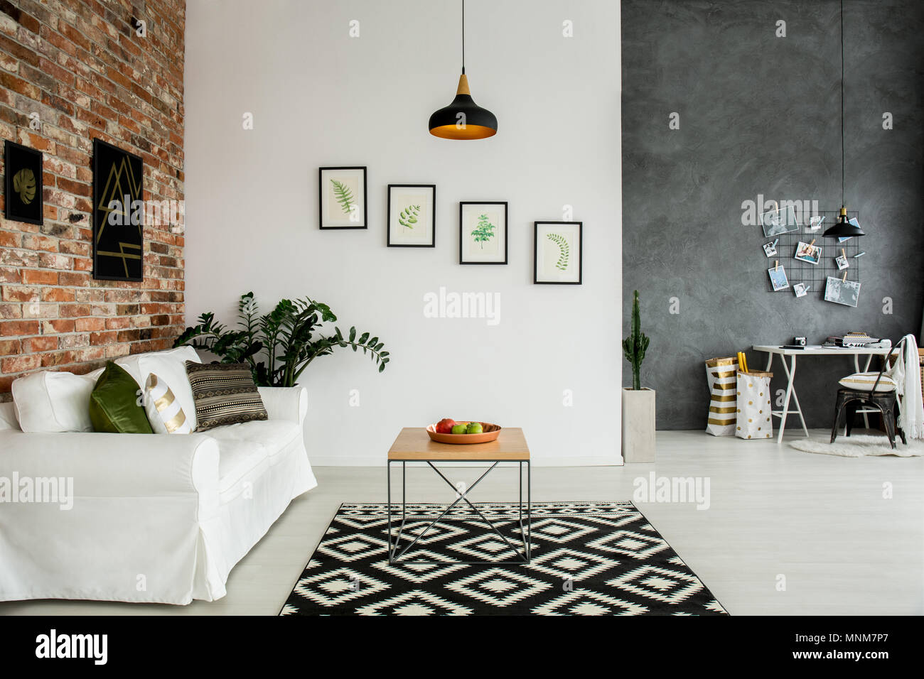Loft interior with open living room and simple home office - Stock Image