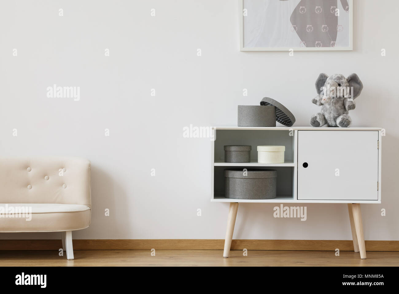 Comfy white small couch standing in kid room with cabinet - Stock Image