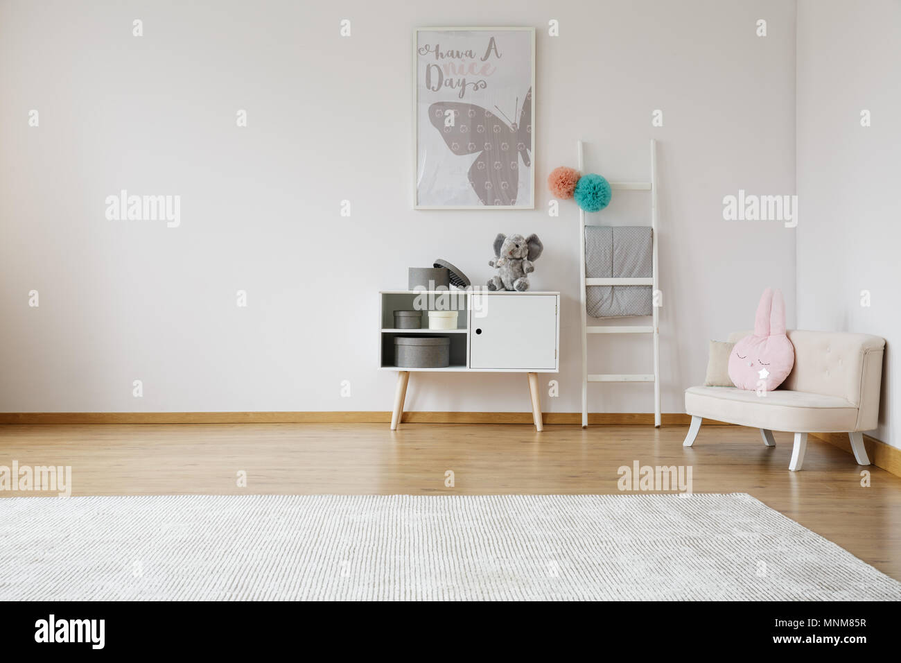 Bright spacious kid room with white cabinet and comfy sofa - Stock Image