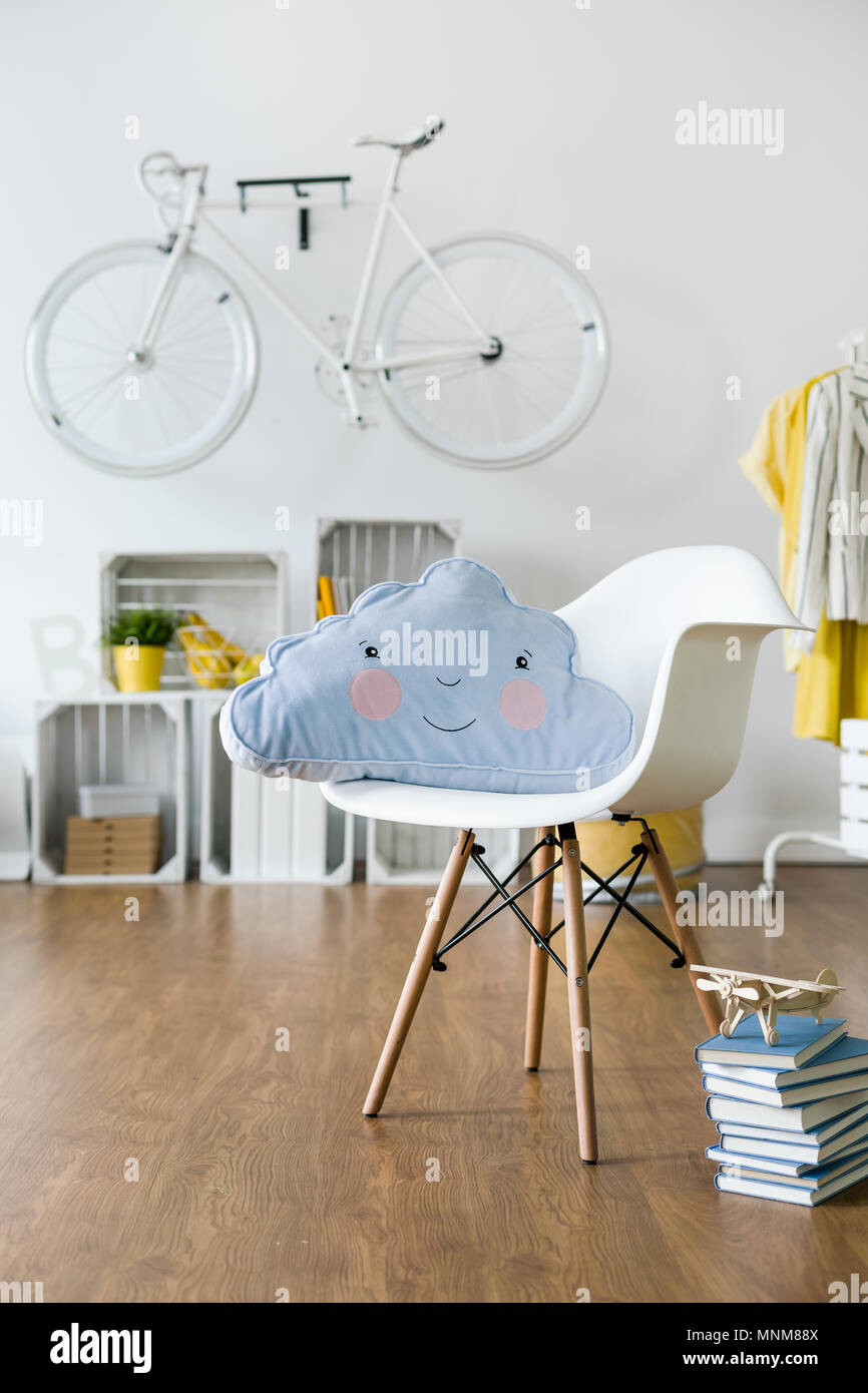 Infantile cushion lying on white chair standing in new, spacious room - Stock Image
