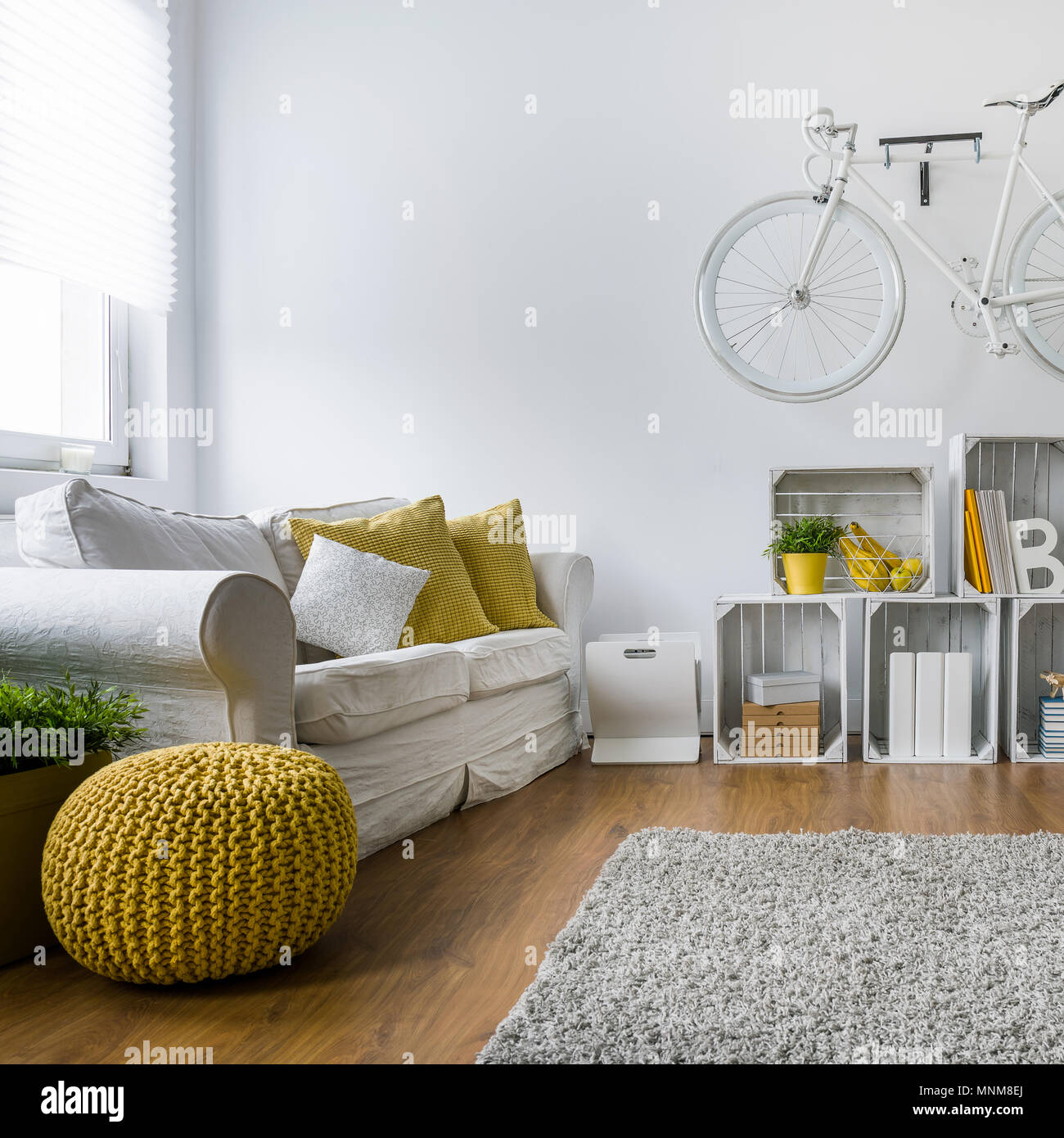 Modern living room with sofa, carpet, wood panels and bike hanging ...