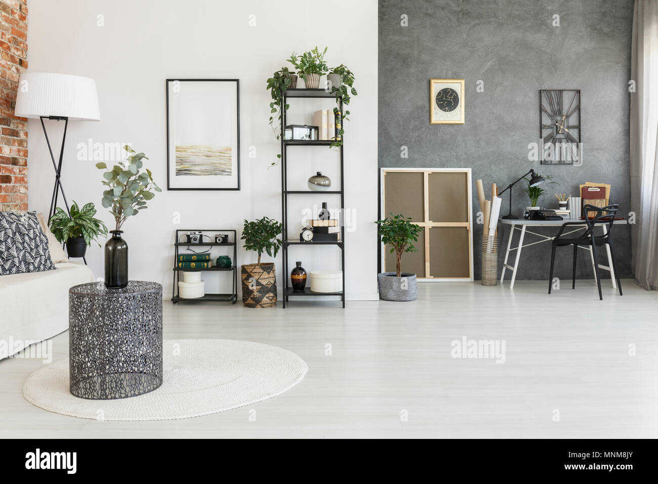 Vase on metal table in open space living room with workspace, plants and contrast colors walls - Stock Image