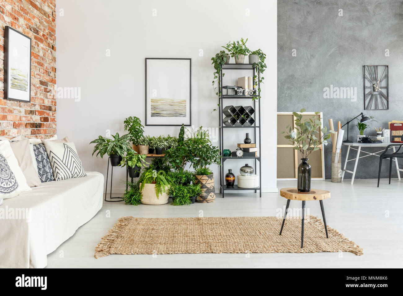 Open space living room on brick wall with  plants and modern study space - Stock Image