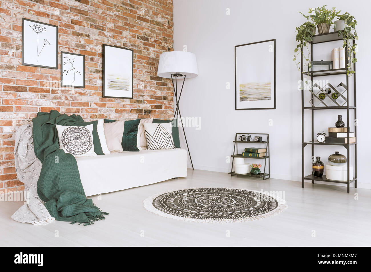 Green blanket on white sofa and pillows in living room with ...