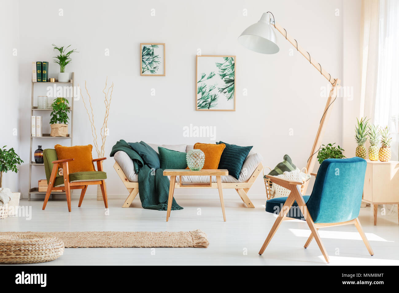 Blue chair and design lamp in natural living room with plants and ...