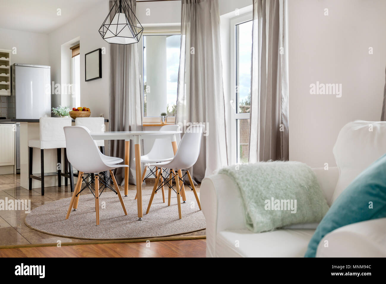New flat with round table, white chairs and open kitchen Stock Photo