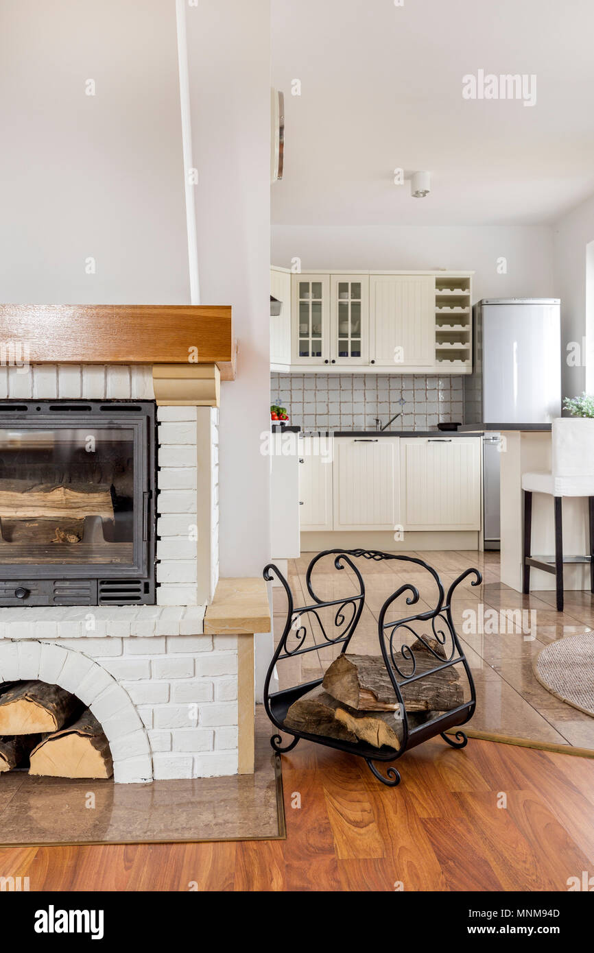 Light home interior with stylish fireplace and open kitchen Stock Photo