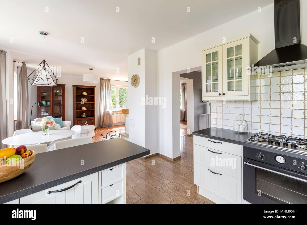 Small white kitchen open to a light dining area Stock Photo