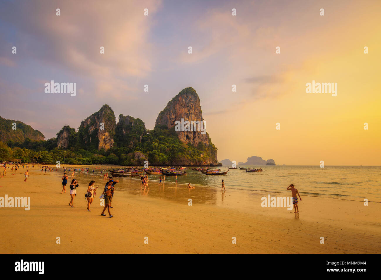 Tourists rest at the Railay Beach before sunset - Stock Image