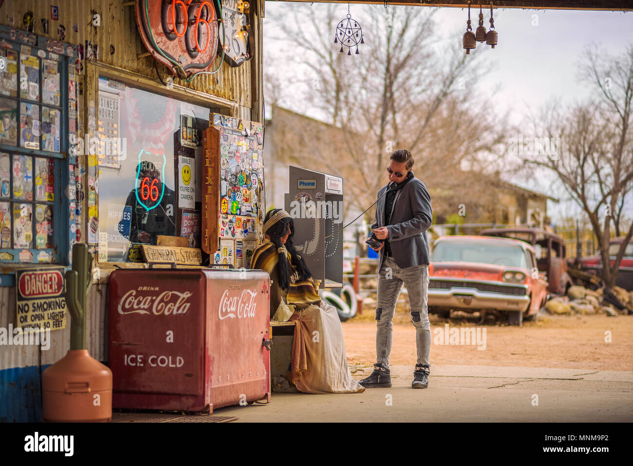 Young man uses a vintage telephone at a retro gas station - Stock Image