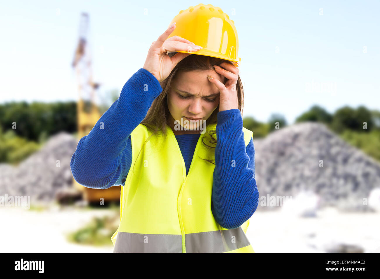 Young female engineer or architect suffering headache because of stressful job as exhausted employee concept on construction site background - Stock Image