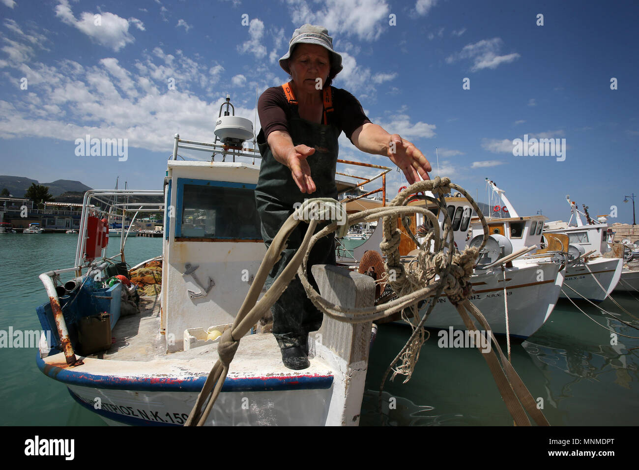 Xylokastro, Peloponnese in Greece. 17th May, 2018. A woman unties the ropes casting off the fishing boat from the marina of Xylokastro, a popular tourist destination of Peloponnese in Greece, May 17, 2018. Due to the economic crisis and over exploitation of the sea, the majority of Greek fishermen is hard to make a living. Credit: Marios Lolos/Xinhua/Alamy Live News Stock Photo