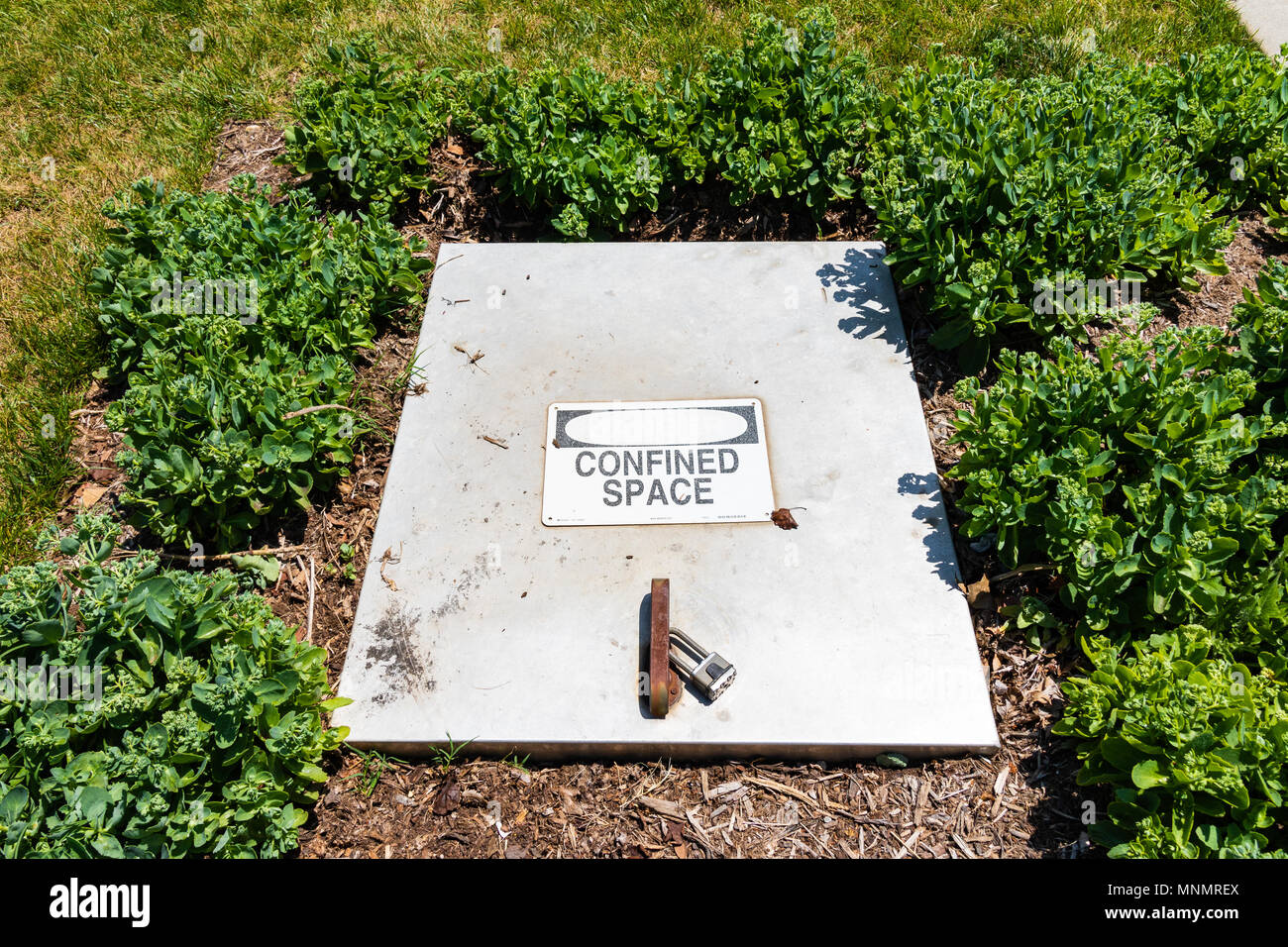 ASHEVILLE, NC, USA-13 MAY 18: Locked rectangular manhole cover with 'confined space' sign on it. - Stock Image